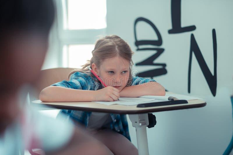 Fundersam skolflicka som tring för att minnas en regelfrome boken fotografering för bildbyråer