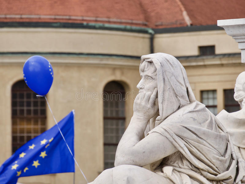 Fundersam staty och EU-symboler arkivbilder