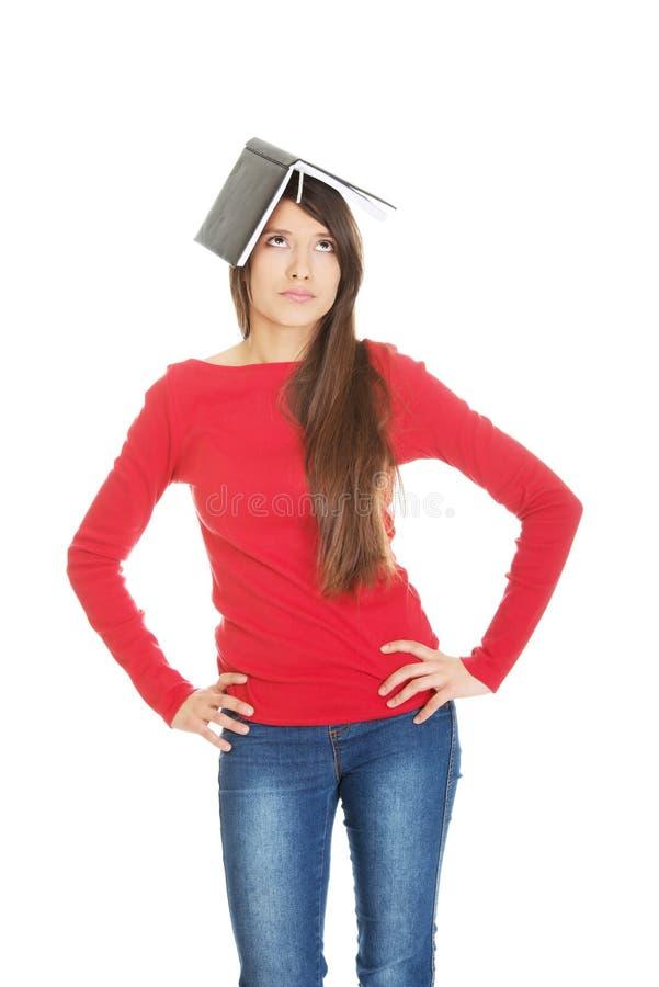 Fundersam studentkvinna med hennes anmärkning på huvudet royaltyfri fotografi