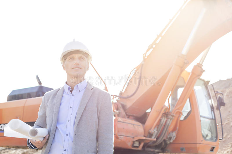 Fundersam tekniker som ser bort, medan rymma gör en skiss av med bulldozern på konstruktionsplatsen royaltyfria foton