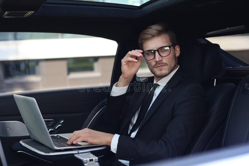 Fundersam ung affärsman som håller handen på exponeringsglas, medan sitta i luxbilen och genom att använda hans bärbar dator arkivbilder
