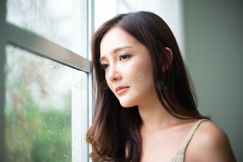 Fundersam ung asiatisk kvinna för Closeup som ser till och med exponeringsglasfönster med regndroppar på hennes hem Melankoliskt  royaltyfria foton