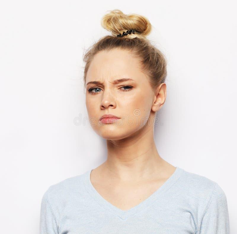 Fundersam ung blond kvinna mot vit bakgrund arkivfoton