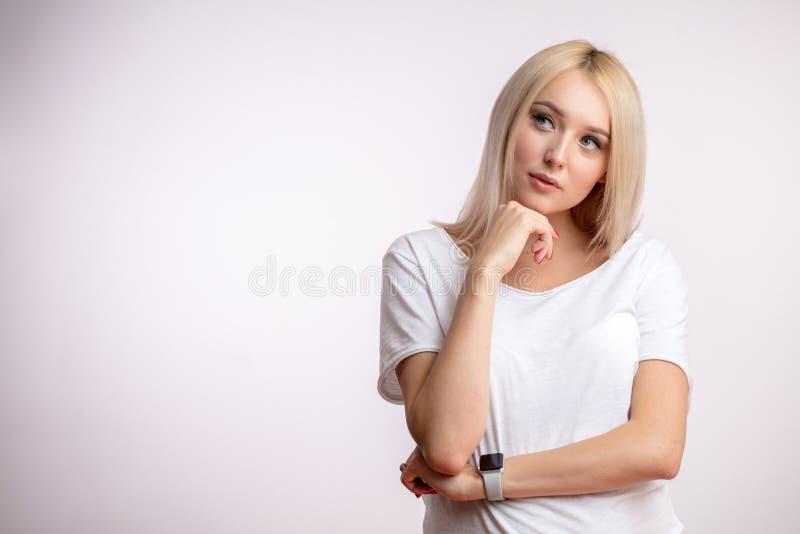 Fundersam ung blondin med handen på hakan fotografering för bildbyråer