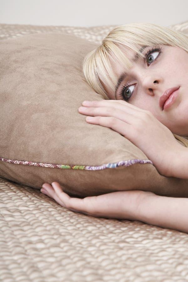 Fundersam ung flicka i liggande säng royaltyfri fotografi