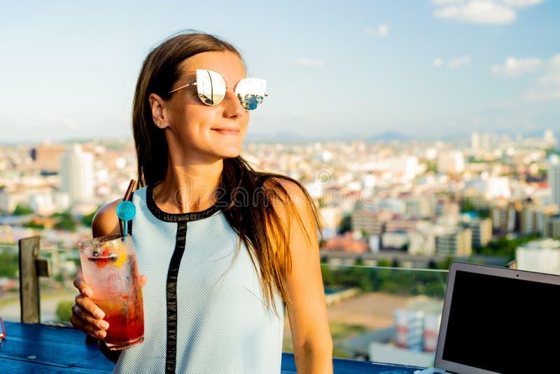 Fundersam ung flicka som dricker smoothiesmoothien Medan sitta på en tabell i ett kafé på taket med ett härligt royaltyfria foton