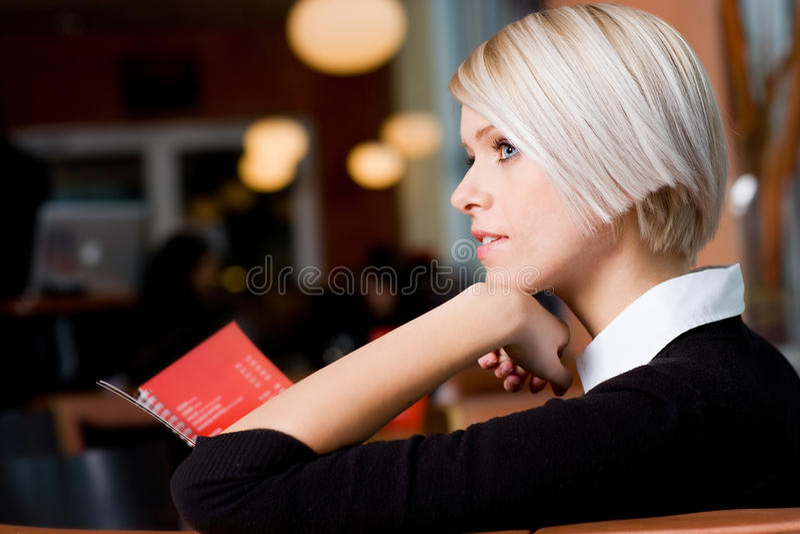 Fundersam ung kvinna i en kafeteria arkivbilder