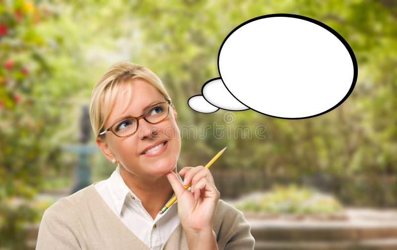 Fundersam ung kvinna med blyertspenna- och mellanrumstankebubblan royaltyfri bild