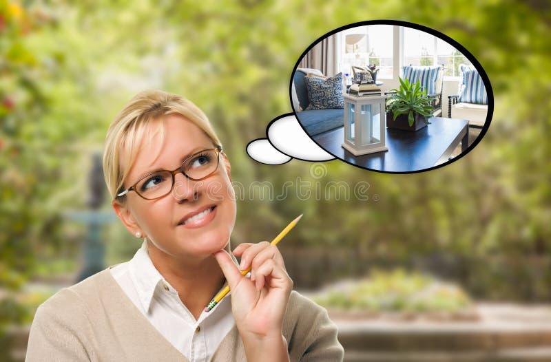Fundersam ung kvinna med blyertspennan och ny vardagsrum in ändå arkivfoto