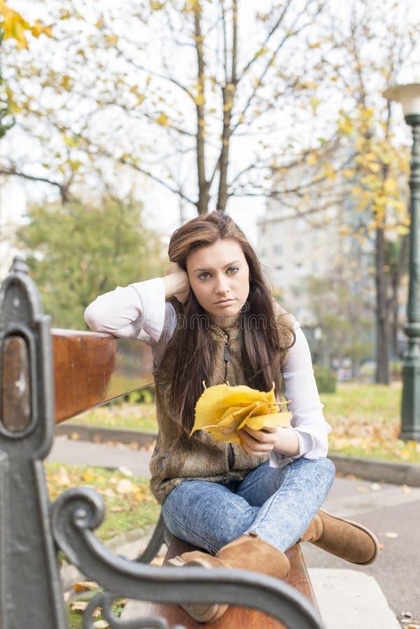 Fundersam ung kvinna med höstsidor på bänk i parkera fotografering för bildbyråer