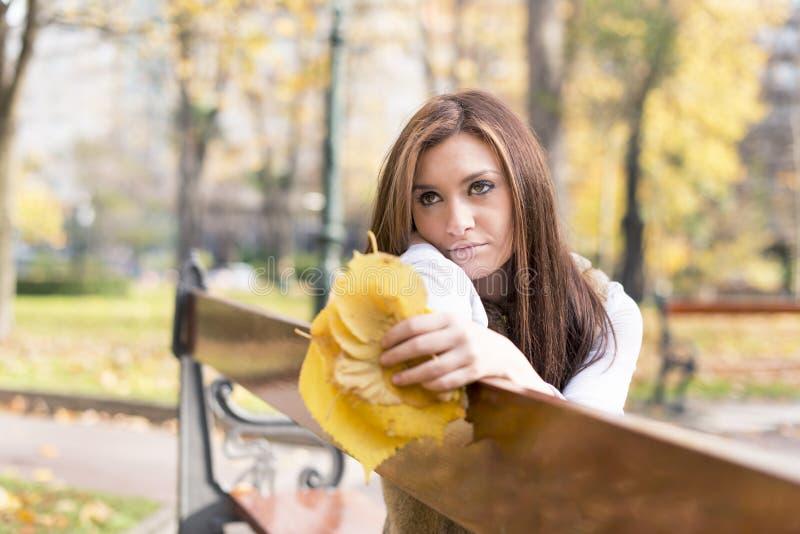 Fundersam ung kvinna med höstsidor på bänk i parkera arkivfoton