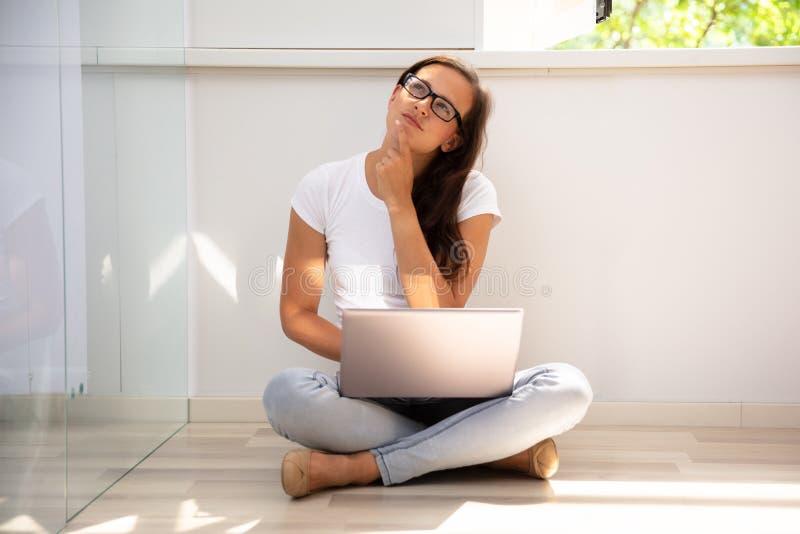 Fundersam ung kvinna som anv?nder b?rbara datorn royaltyfri fotografi