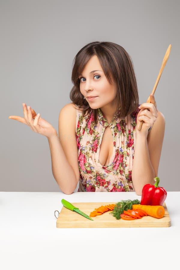 Fundersam ung kvinna som hugger av grönsaker arkivfoton