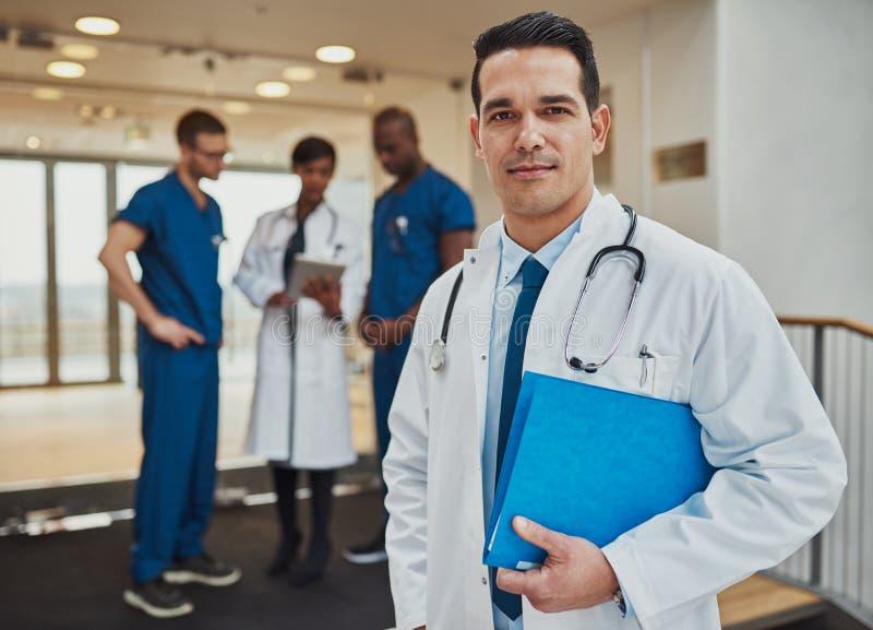 Fundersam ung latinamerikansk doktor i ett sjukhus fotografering för bildbyråer