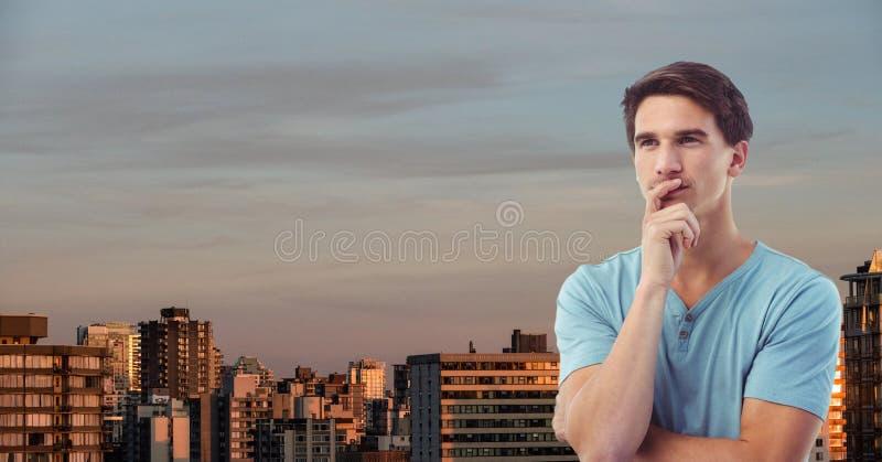 Fundersam ung man i stad mot himmel arkivfoton