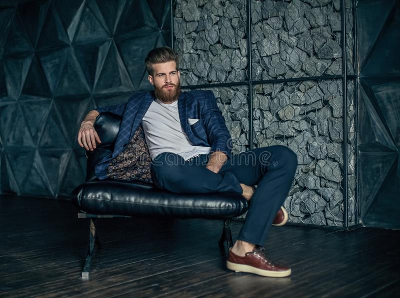 Fundersam ung modern man som sitter på hans arbetsplats royaltyfri foto