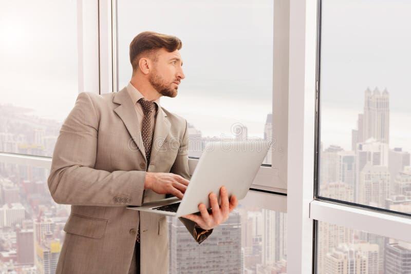 Fundersam vuxen affärsman som arbetar i kontoret arkivbilder