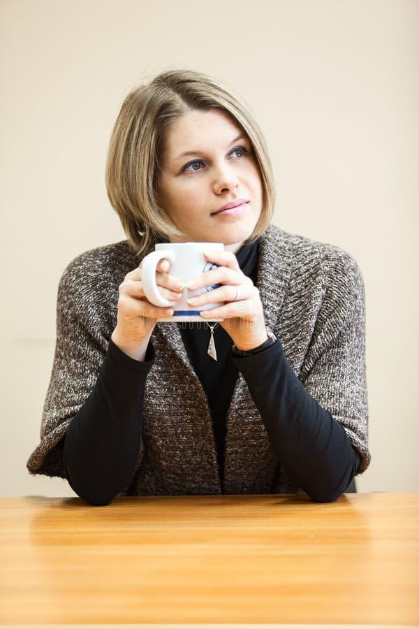 Fundersam yong kvinna som dricker kaffe arkivfoto