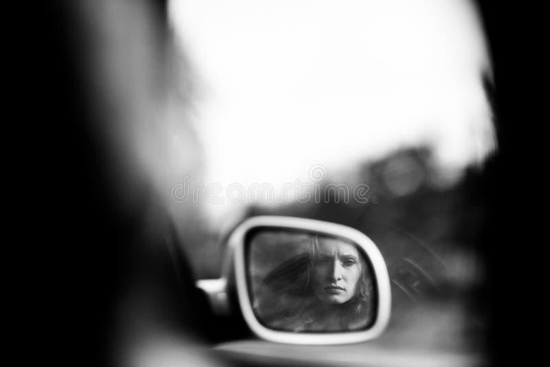Fundersamma kvinnans framsida reflekterar i bilarna tillbaka avspeglar royaltyfri bild