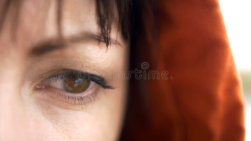 Fundersamma seende ögon för ung kvinna som är bruna i kontaktlinser I den orange huven på huvudet Se i väg från arkivfoto