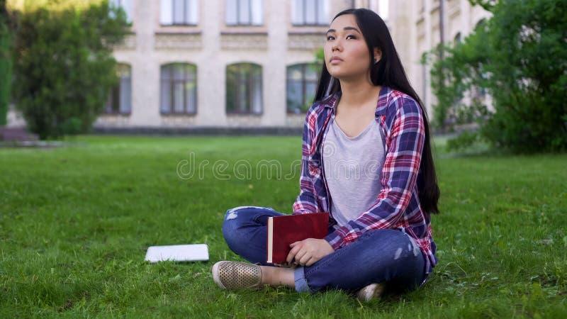 Fundersamt asiatiskt sammanträde för kvinnlig student på gräsmatta bara och missande föräldrar fotografering för bildbyråer