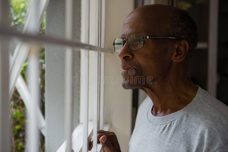 Fundersamt bärande glasögon för hög man, medan se ut till och med fönster royaltyfri bild