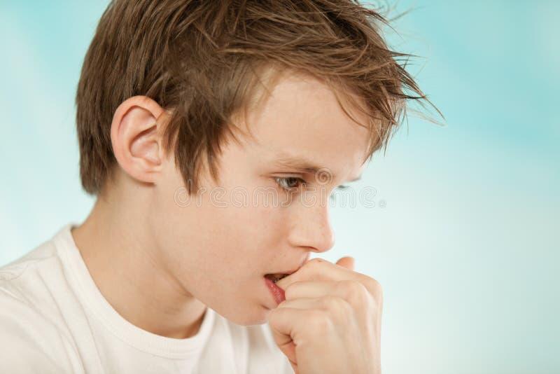 Fundersamt bekymrat ungt bita för pojke som är hans, spikar royaltyfri fotografi