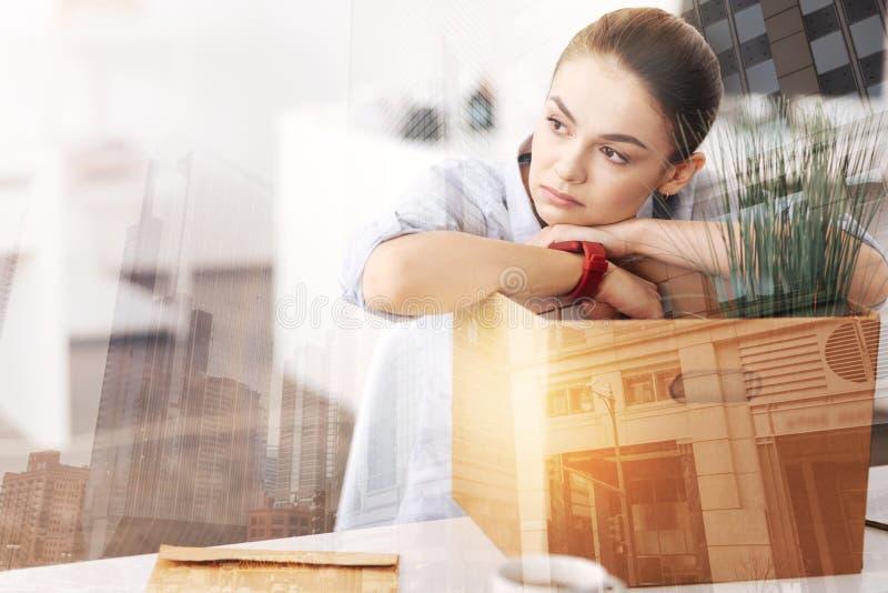 Fundersamt dystert kvinnasammanträde i kontoret med hennes tillhörigheter fotografering för bildbyråer