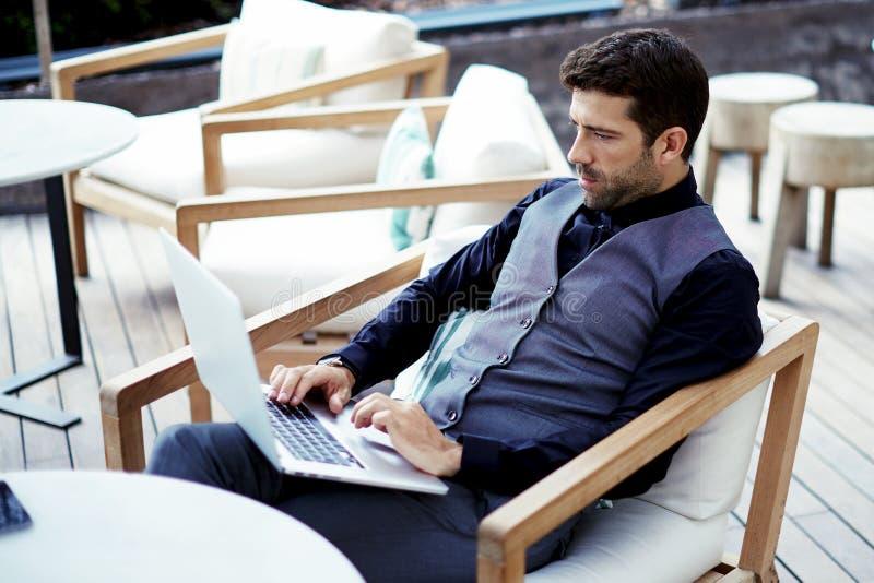 Fundersamt förmöget affärsmanarbete som är on-line på netto-boken, medan sitter på den moderna restaurangterrassen arkivbilder