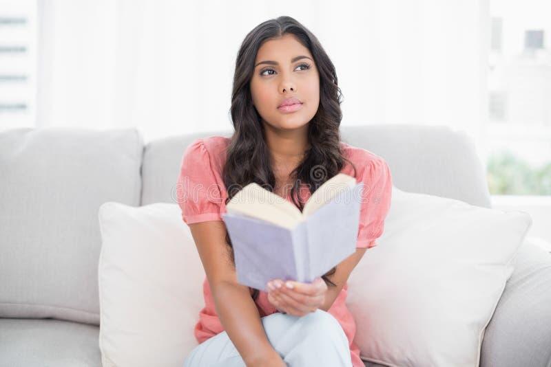 Fundersamt gulligt brunettsammanträde på soffan som läser en bok royaltyfria foton