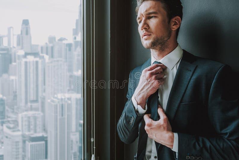 Fundersamt mananseende nära fönstret och trycka på hans band royaltyfria foton
