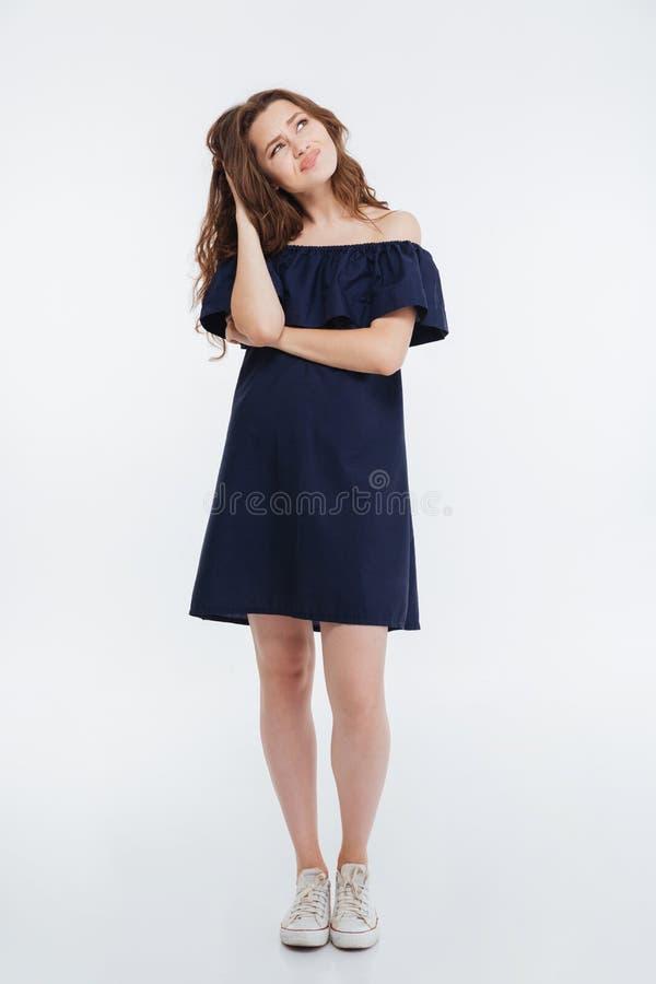 Fundersamt rynka pannan anseende och tänka för ung kvinna royaltyfri foto