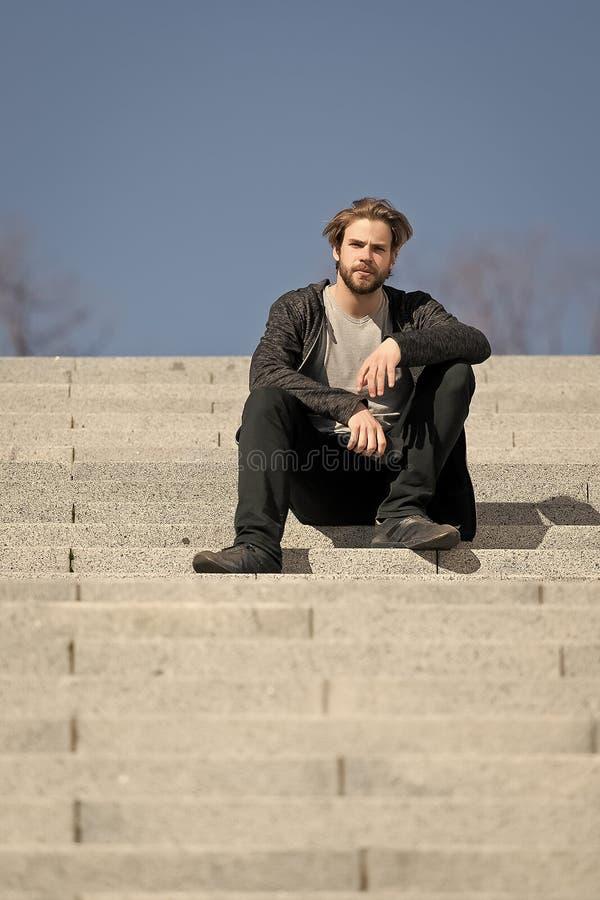Fundersamt sammanträde för ung man på moment mot bakgrund för blå himmel royaltyfri foto
