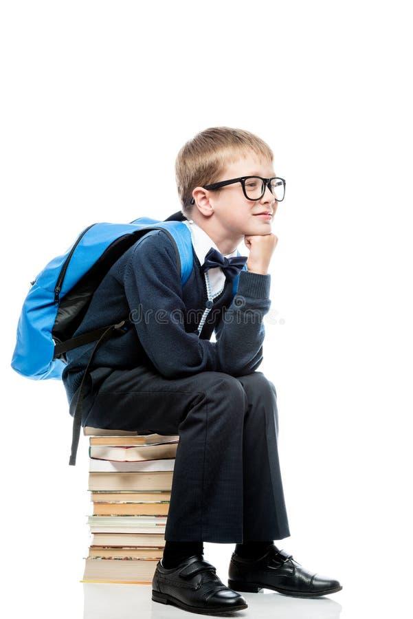 Fundersamt skolpojkesammanträde på en hög av böcker på en vit backg arkivbild