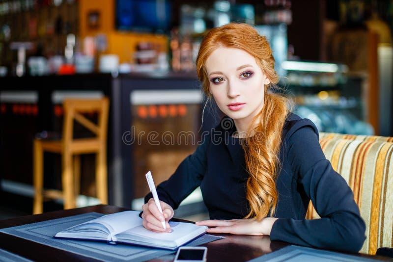Fundersamt ungt affärskvinnasammanträde i ett kafé och en handstil i notepad royaltyfri foto
