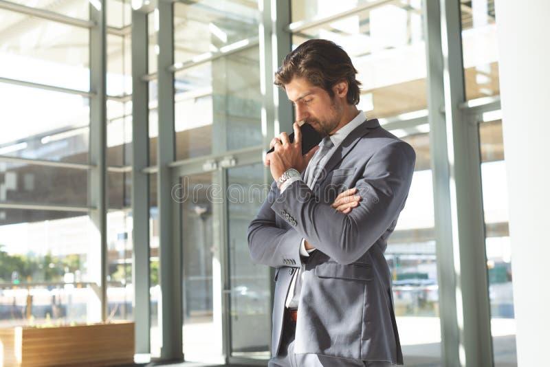 Fundersamt ungt affärsmanhuvud ner på hans mobiltelefonanseende i lobbykontor arkivfoto
