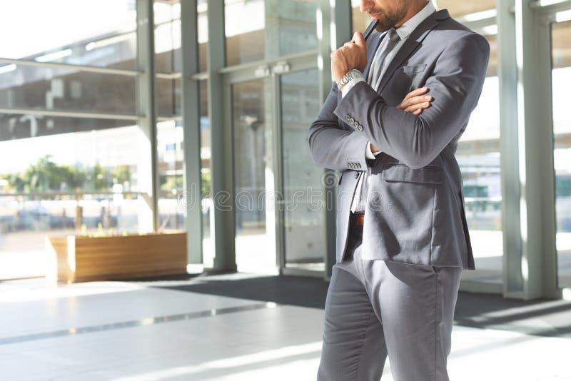 Fundersamt ungt affärsmanhuvud ner på hans mobiltelefonanseende i lobbykontor royaltyfria bilder