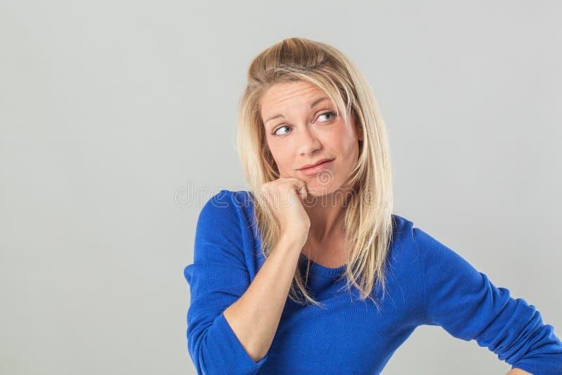 Fundersamt ungt blont dagdrömma för kvinna som ser i väg från fel fotografering för bildbyråer