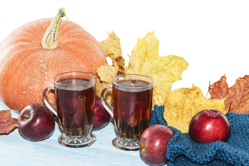 Fundo, abóbora, maçãs com folhas amarelas e chá do outono no copo na tabela de madeira no fundo branco fotos de stock royalty free