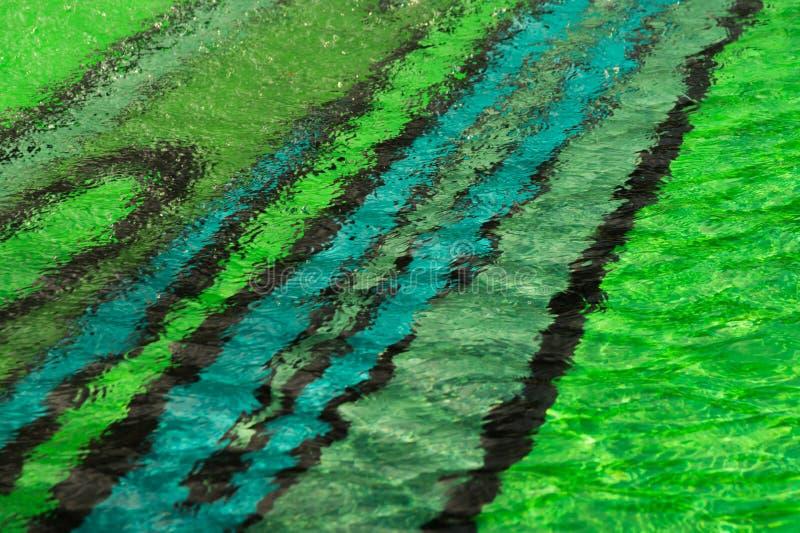 fundo abstrato da água colorida da associação parte inferior colorida da piscina com água rippled fotografia de stock