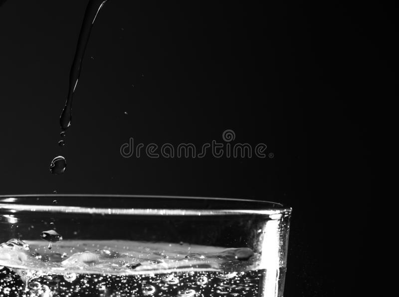 Fundo abstrato da água que está sendo derramada ao vidro Gotas da ?gua O pico do vidro encheu-se com água e os sparkles são visív fotos de stock royalty free