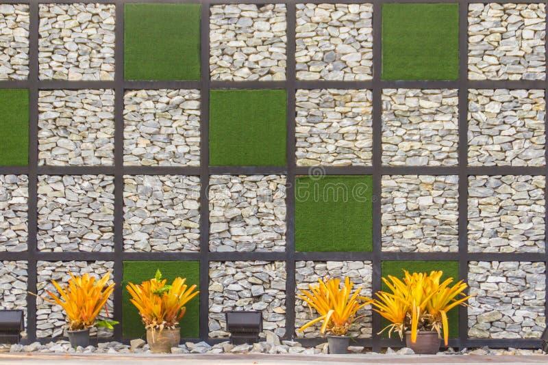 Fundo abstrato da parede de pedra do seixo do rio com quadro da grama verde Cobrir a forma do fundo da parede e do quadrado da gr fotografia de stock royalty free