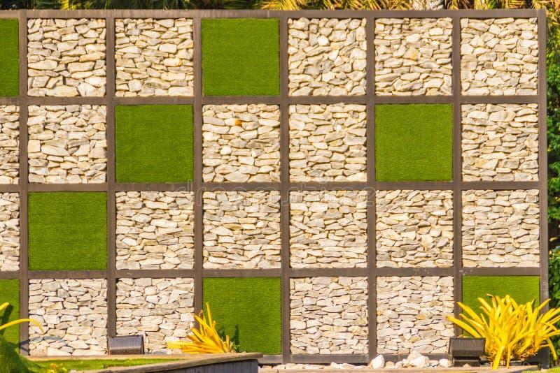 Fundo abstrato da parede de pedra do seixo do rio com quadro da grama verde Cobrir a forma do fundo da parede e do quadrado da gr fotos de stock