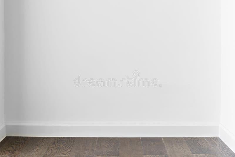 Fundo abstrato do muro de cimento branco vazio em casa ou escrit?rio com assoalho de madeira A imagem para adiciona a mensagem de imagem de stock royalty free