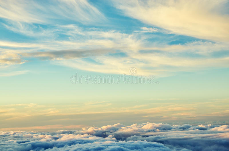 Fundo abstrato do ouro e das nuvens azuis das cores Céu do por do sol acima das nuvens imagens de stock