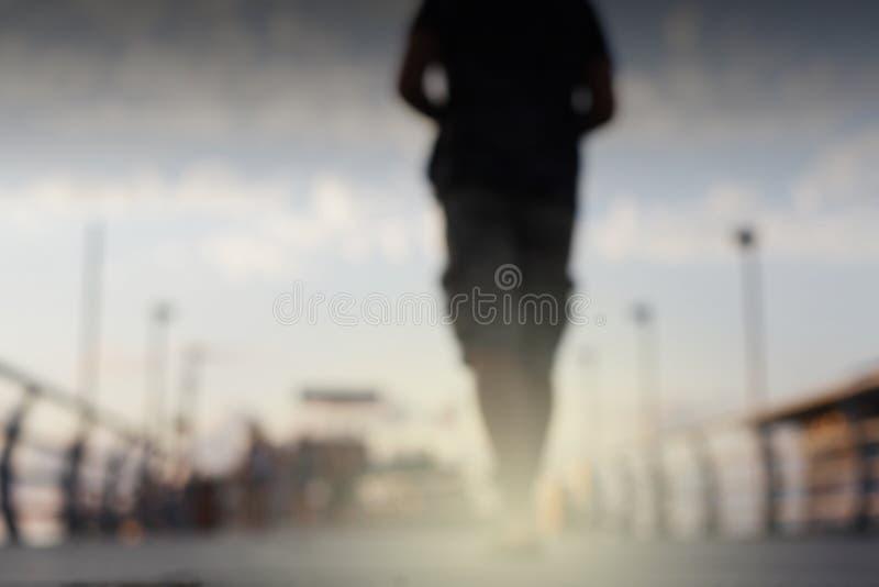 Fundo abstrato piscar do borrão da luz da cidade da rua Foco macio Silhueta do homem fotografia de stock royalty free