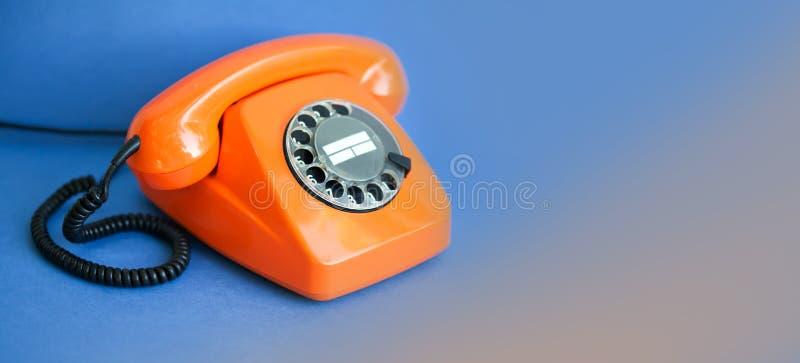 Fundo alaranjado do azul do telefone Conceito plástico do centro de atendimento de uma comunicação do receptor do monofone do est foto de stock
