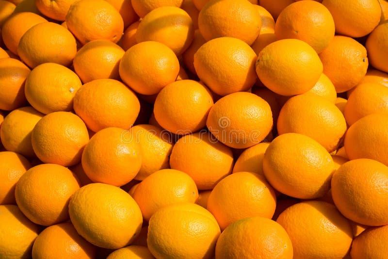 Fundo alaranjado do fruto - muitos frutos da laranja - fotografia de stock