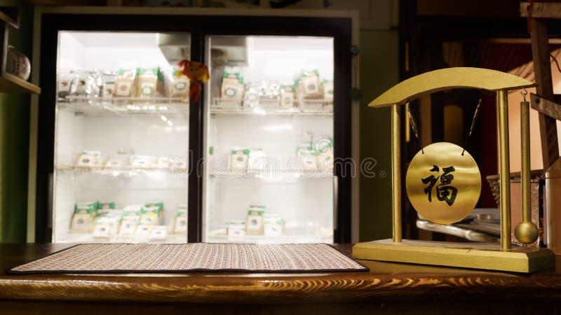 Fundo borrado cafetaria do chá, barra de madeira Esteira e sino de bambu do serviço com desejos do caráter chinês da felicidade,  fotos de stock
