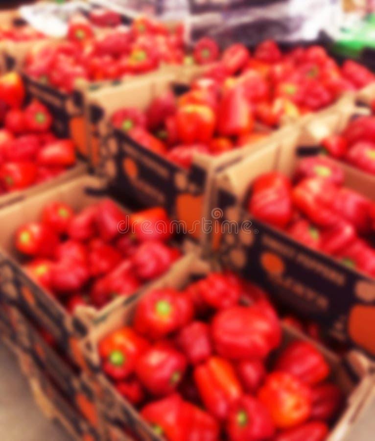 Fundo borrado com as vagens frescas da loja do supermercado das pimentas vermelhas i Fim acima Luzes do bokeh do borrão Supermerc imagem de stock